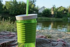 Grünes Plastikglas mit einem Getränk und ein Rohr auf dem Strand nahe dem Wasser lizenzfreie stockfotografie