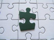 Grünes Puzzlespielstück Stockfotos