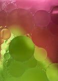 Grünes, rosa Steigungs-Öl fällt in das Wasser - abstrakter Hintergrund Stockbild