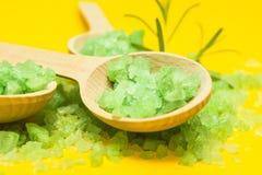 Grünes Salz in drei hölzernen Löffeln auf einem gelben Hintergrund Gemüsebestandteile für Hautpflege stockfotos