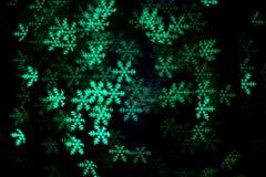 Grünes Schneeflocke bokeh in der Dunkelheit Stockfotografie