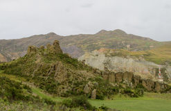 Grünes Tal und Felsformationen unter bewölktem Himmel Lizenzfreies Stockfoto
