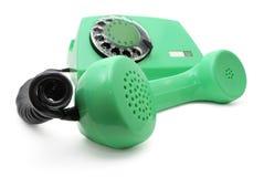 Grünes Telefon mit einer Platte Stockfoto