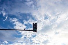 Grünes Traffice-Licht auf blauem Himmel mit Wolke Stockfotos