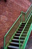 Grünes Treppenhaus auf Backsteinmauer Stockfoto