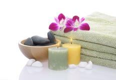 Grünes Tuch, Orchidee, Kerzen und Kiesel Stockfoto