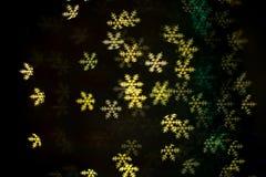 Grünes und gelbes Schneeflocke bokeh in der Dunkelheit Lizenzfreie Stockbilder