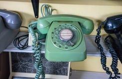 Grünes und schwarzes Weinlesetelefon auf hölzernem Regal stockfotografie