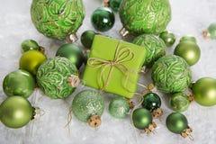 Grünes und weißes Weihnachtshintergrund mit Geschenkbox, Schnee und bal lizenzfreies stockbild