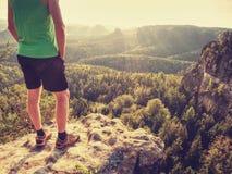 Grünes Unterhemd und furchtloser Junge der Schwarzhosen in den Felsen Erstaunliche Ansicht lizenzfreies stockbild