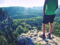 Grünes Unterhemd und furchtloser Junge der Schwarzhosen in den Felsen Erstaunliche Ansicht stockbilder
