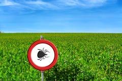 Grünes Warnzeichen des Feldes und der Zecke Stockbild