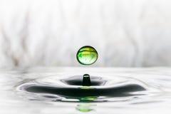 Grünes Wassertropfenaufprallen lizenzfreie stockbilder