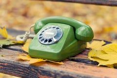 Grünes Weinlesetelefon auf Bank Stockbilder
