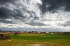 Grünfelder und ein kleines Dorf mit einem bewölkten Himmel Stockbild