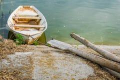 Grünlicher schlammiger Fluss des alten hölzernen Bootes Nahe bei dem alten hölzernen Ruder Lokale und ländliche Landschaft stockfotos