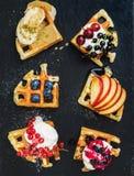 Grże belgijskich domowej roboty gofry z świeżymi ogrodowymi jagodami, owoc i lody na zmroku łupku kamienia tle, Fotografia Royalty Free