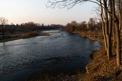 Grże krajobrazowego zmierzch przy rzeką z działającą wiosny wodą w Bauska, Latvia, 2019 zdjęcia royalty free