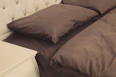 Gr?a b?dda ned ark, filt och kuddar i hotellrummet Vila och att sova, komfortbegreppet Kudde p? s?ngen Bild av royaltyfria foton