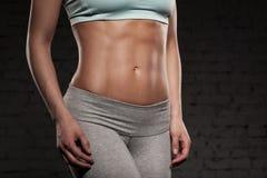 Gör den kvinnliga kvinnan för kondition med den muskulösa kroppen, hennes genomkörare, abs, abdominals Fotografering för Bildbyråer