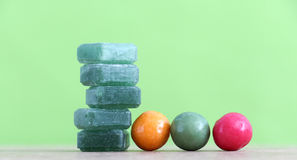 Gr een mints candy and bubble gum on green background. Stock Photos