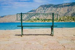 Gr?n b?nk f?r metall p? stranden med havs- och bergsikt royaltyfria bilder