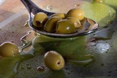 Gr?na oliv i en sked arkivfoto