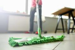 Gr?ner Plastikmop, der lamellierten hellen schmutzigen Boden s?ubert lizenzfreies stockbild