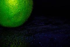 Gr?ner reifer Apfel mit Wassertr?pfchen auf einem dunklen Hintergrund, Nahaufnahme lizenzfreie stockfotos