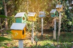 Gr?nes und gelbes h?lzernes Vogelhaus auf Posten im Garten auf Sommer- oder Fr?hlingssonnenschein mit nat?rlichem gr?nem Blatthin lizenzfreie stockfotografie