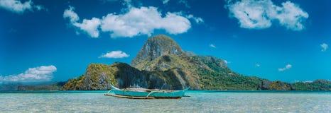 Gr Nido, de boot van vissers in blauwe baai met panorama van Cadlao-Eiland op achtergrond, Palawan, Filippijnen royalty-vrije stock foto's