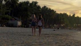 Gr Nido, Filippijnen - Februari 2, 2019: Achtermening van mooie jonge meisjes die op het tropische strand bij zonsondergang lopen stock videobeelden