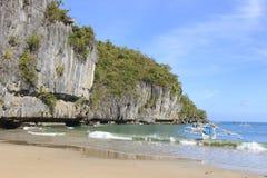 Gr Nido, Filippijnen - Januari 11.2015: Tropisch strand in Gr Nido, Palawan, met een bootmens op een tipical Philippinos-boot Stock Foto