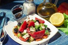 Gr?nsaksallad i bunke p? den bl?a tr?tabellen Smaklig grekisk sallad med feta, oliv och tomater i en bunke brigham arkivbilder