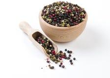 Gr?os de pimenta coloridos da pimenta na bacia de madeira e na colher isoladas no fundo branco Especiarias e ingredientes de alim foto de stock