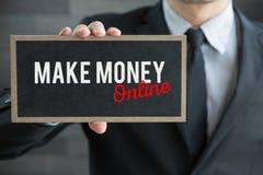 Gör pengar online-, meddelandet på det vita kortet och hållen av affärsmannen Royaltyfria Bilder