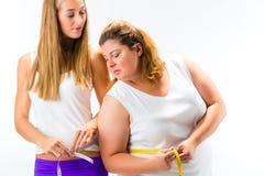 Gör tunnare och den feta kvinnan som mäter midjan med bandet Royaltyfria Bilder