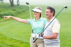 Grać w golfa pary uśmiecha się kluby i trzyma Zdjęcia Royalty Free