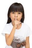 Göra en gest tystnadtecken för liten flicka Arkivfoton