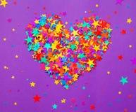 Gra główna rolę confetti na purpurowym tle, serce Zdjęcia Royalty Free