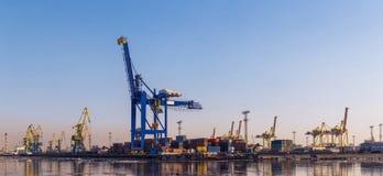 Grúa grande del cargo, tren de carga y muchos envases en puerto Foto de archivo libre de regalías