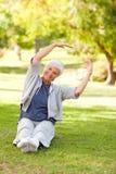göra henne sträcker pensionären kvinnan Arkivbild