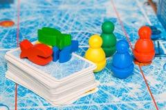 Gra planszowa i dzieciaka czasu wolnego pojęcie czerwień, kolor żółty, błękit, zieleni drewniani układy scaleni postać i karty do obrazy royalty free
