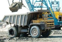 Graafwerktuig die een zware stortplaatsvrachtwagen laden Stock Afbeeldingen