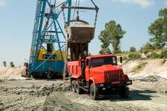 Graafwerktuig die een zware stortplaatsvrachtwagen laden Royalty-vrije Stock Foto