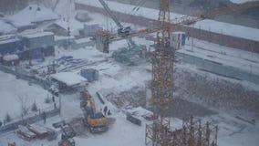 Graafwerktuig en een kraan die aan een bouwwerf tijdens een sneeuwblizzard werken, 4k stock footage