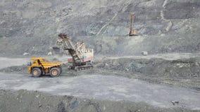 Graafwerktuig en stortplaatsvrachtwagen terwijl het laden van steenerts in een grijze steengroeve, mijnbouw voorraad De zware lad stock fotografie