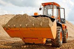 Graafwerktuig met zand in de emmer Stock Fotografie