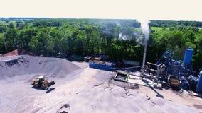 Graafwerktuig op de asfaltinstallatie met een grote berg van puin In aanbouw stock videobeelden
