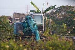 Graafwerktuigtractor die aan moddergrond werken met boom stock foto